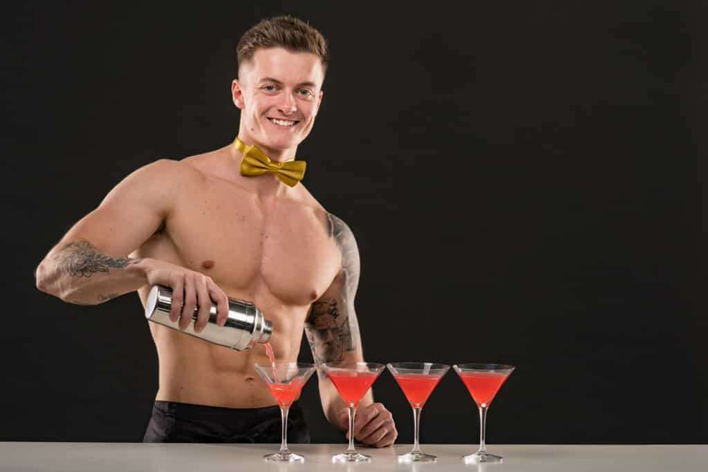 A topless waiter preparing cocktails for guests.