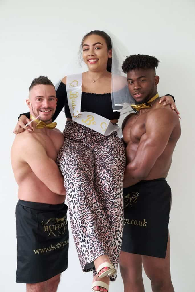 Two buff butlers holding the bride to be